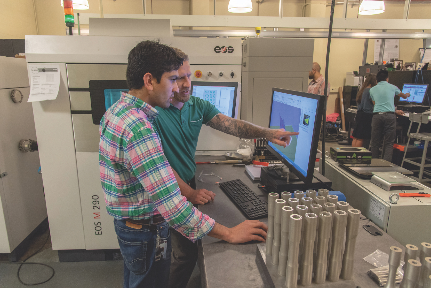 Mechanical engineering doctoral students Basil Paudel (left) and Jonathan Pegues look at a 3-D computer-aided design model in the additive manufacturing lab in Wiggins Hall.